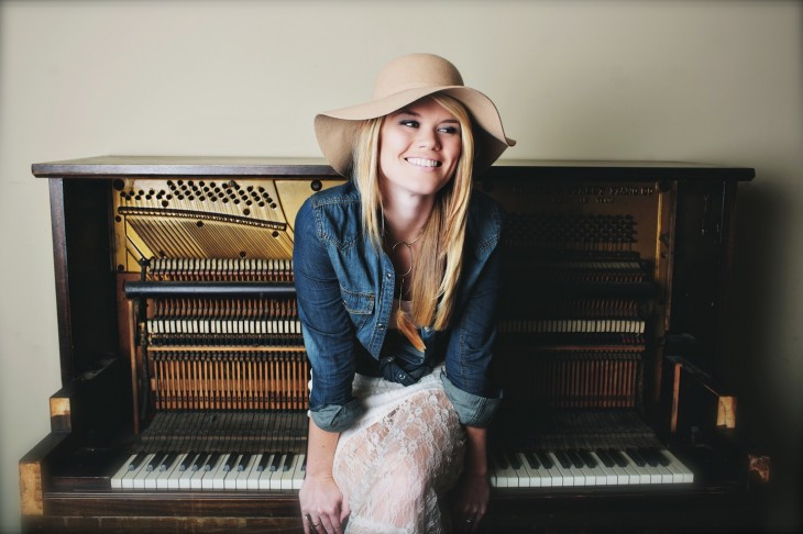 Nicolle Galyon is wearing a round hat while sitting on a piano